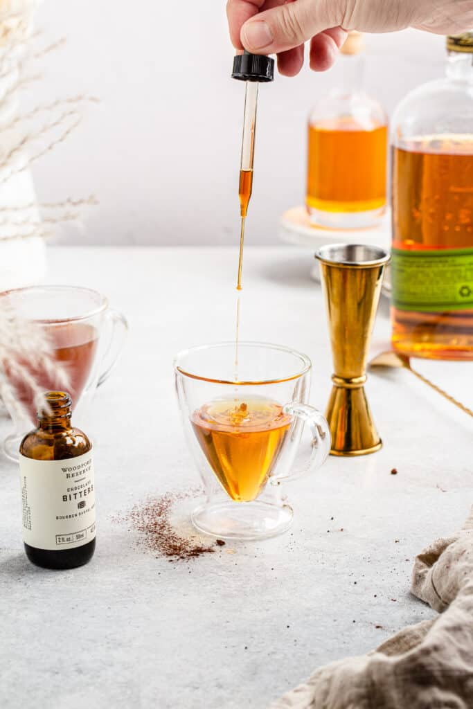 adding chocolate bitters from dropper into cocktail