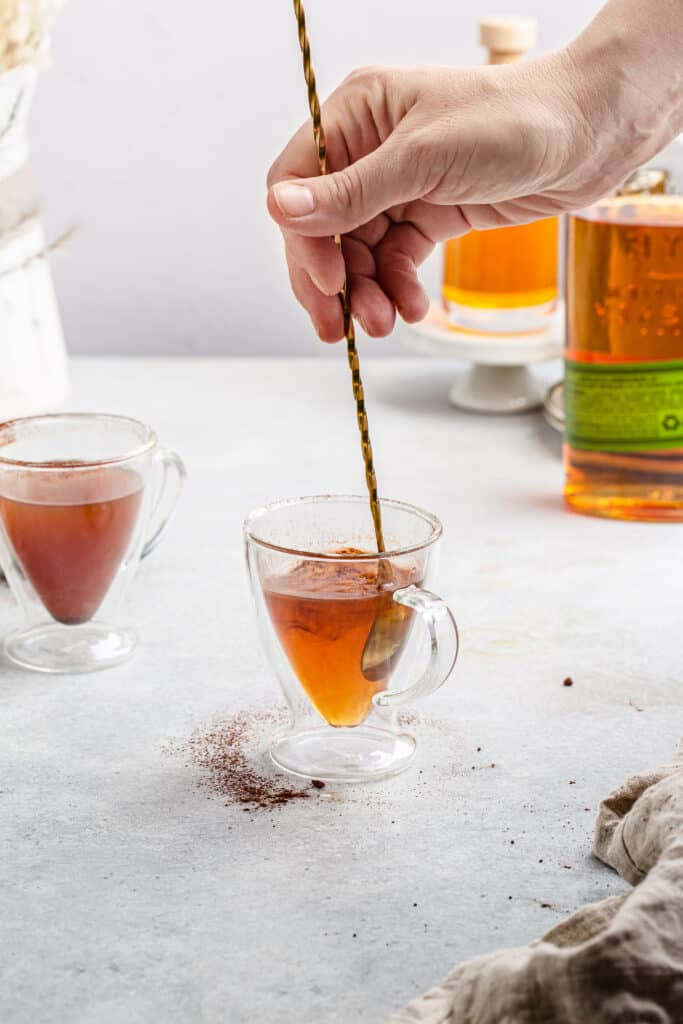 stirring whiskey and caramel cocktail