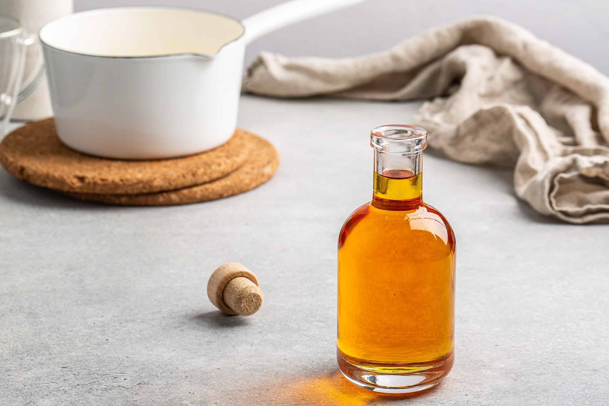 horizontal shot of caramel syrup in a bottle with white pan in background