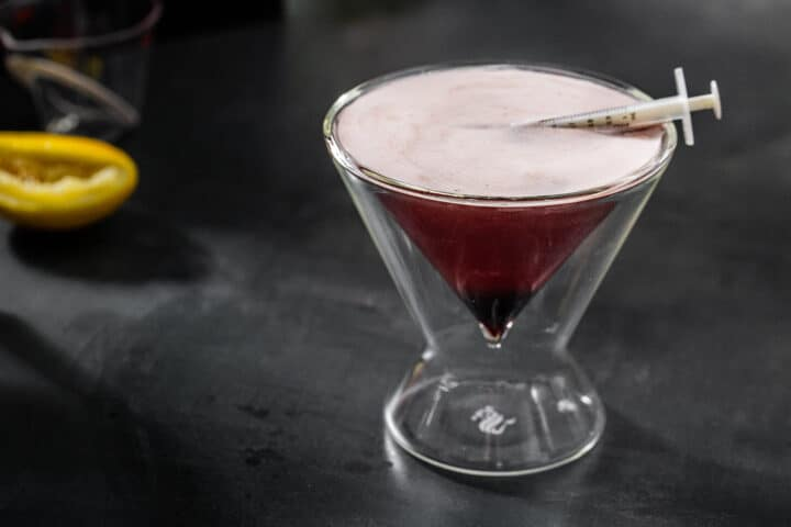 horizontal image of bloody shiraz sour with medicine dropper and squeezed lemon in the background