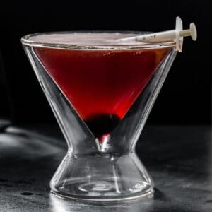 side view of red cocktail in a double-walled martini glass