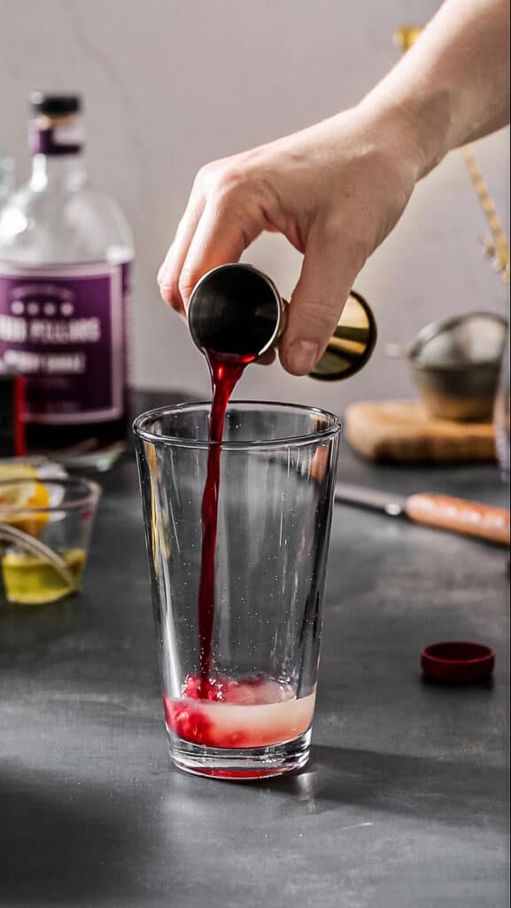 pouring pomegranate juice into cocktail