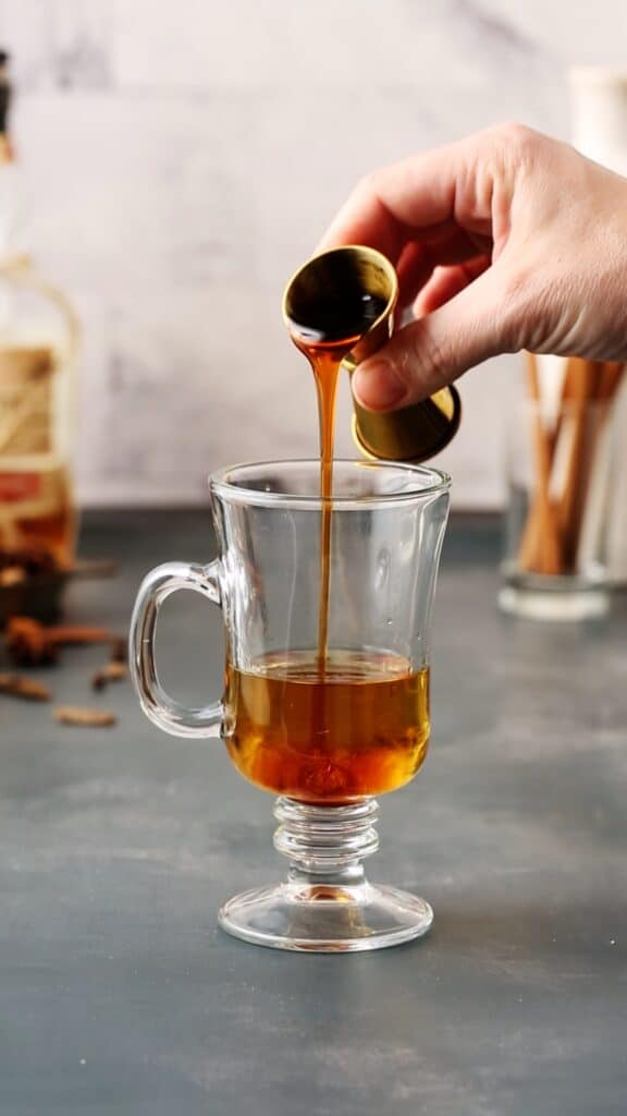 pouring apple cider concentrate into cocktail glass