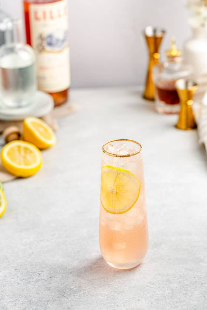 top view of lillet gin cocktail with lemons and other ingredients in the background