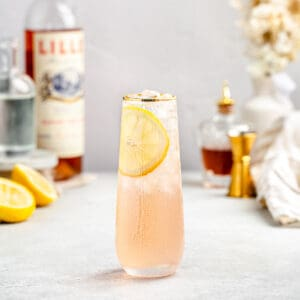 side view of lillet gin cocktail in a stemless champagne glass with gold rim