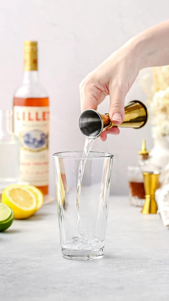 adding gin to the cocktail shaker