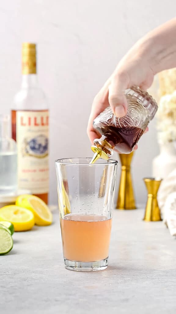 adding bitters to the cocktail shaker