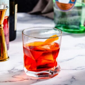 Close up of a Negroni cocktail, a red-colored drink in an old fashioned glass with a large piece of orange peel