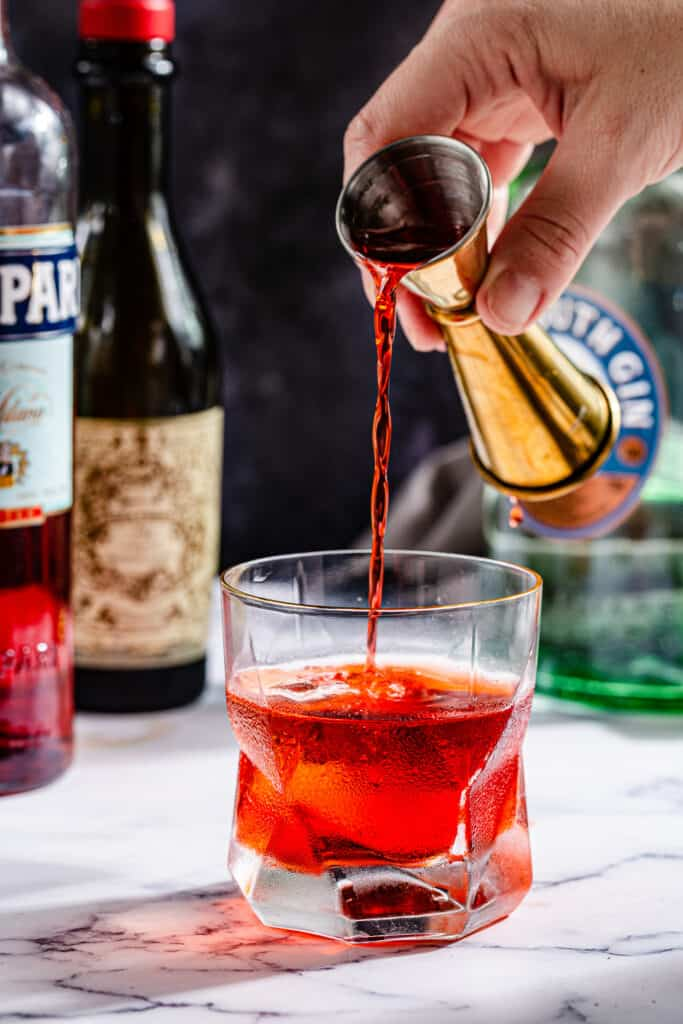 pouring Campari into the cocktail glass
