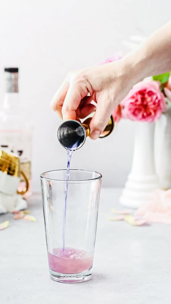 pouring clear gin into cocktail shaker