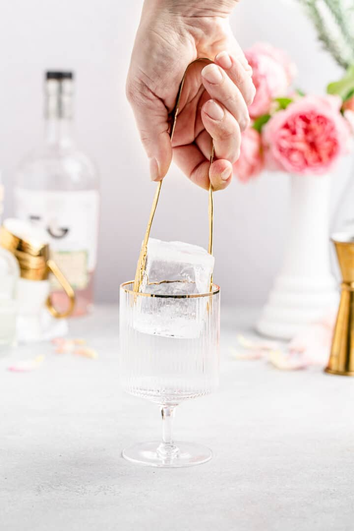 adding large clear ice to gold-rimmed cocktail glass