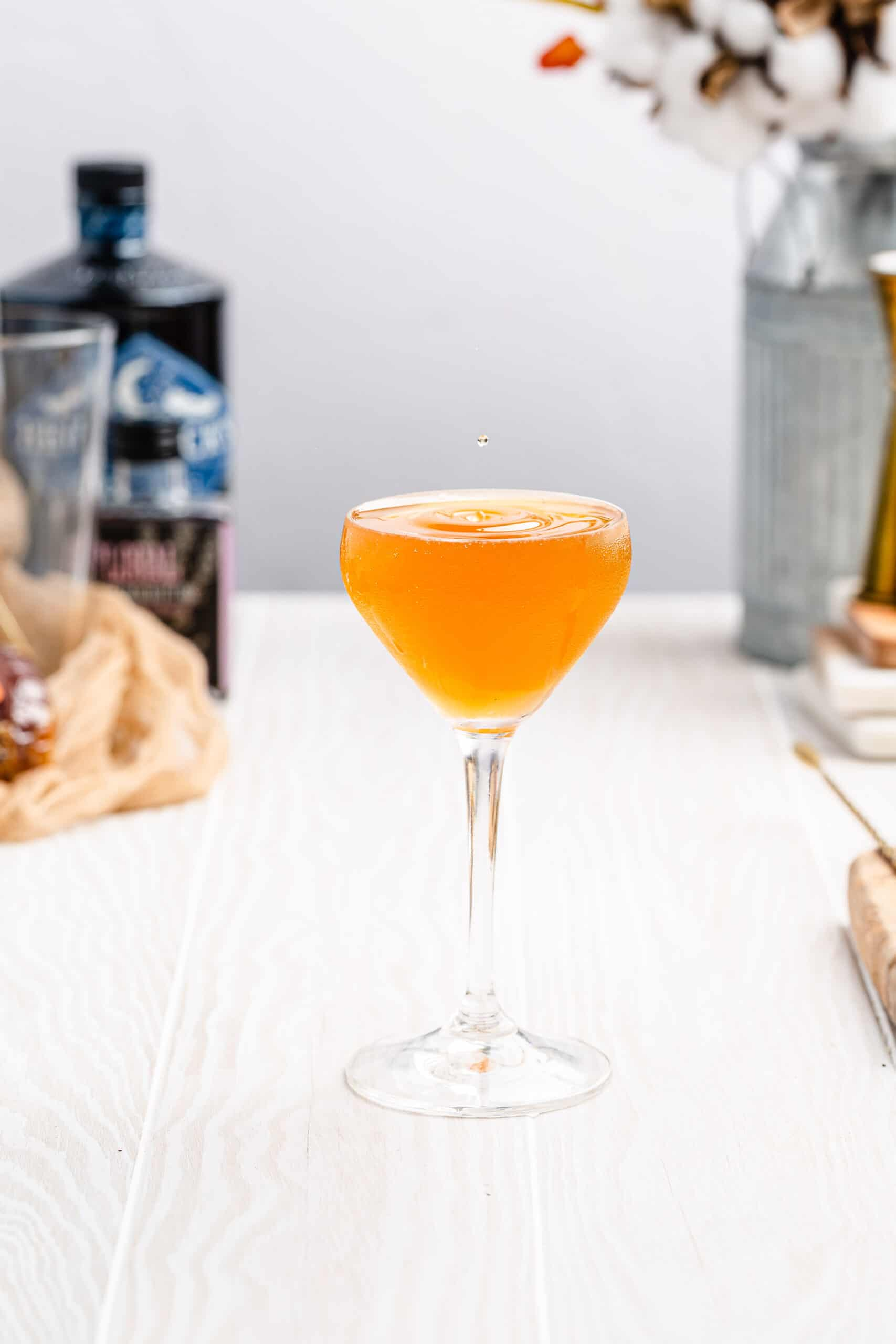 vertical image of bees knees cocktail in a stemmed cocktail glass with ingredients in the background