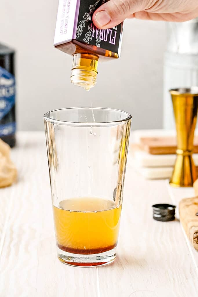 adding floral bitters to cocktail shaker