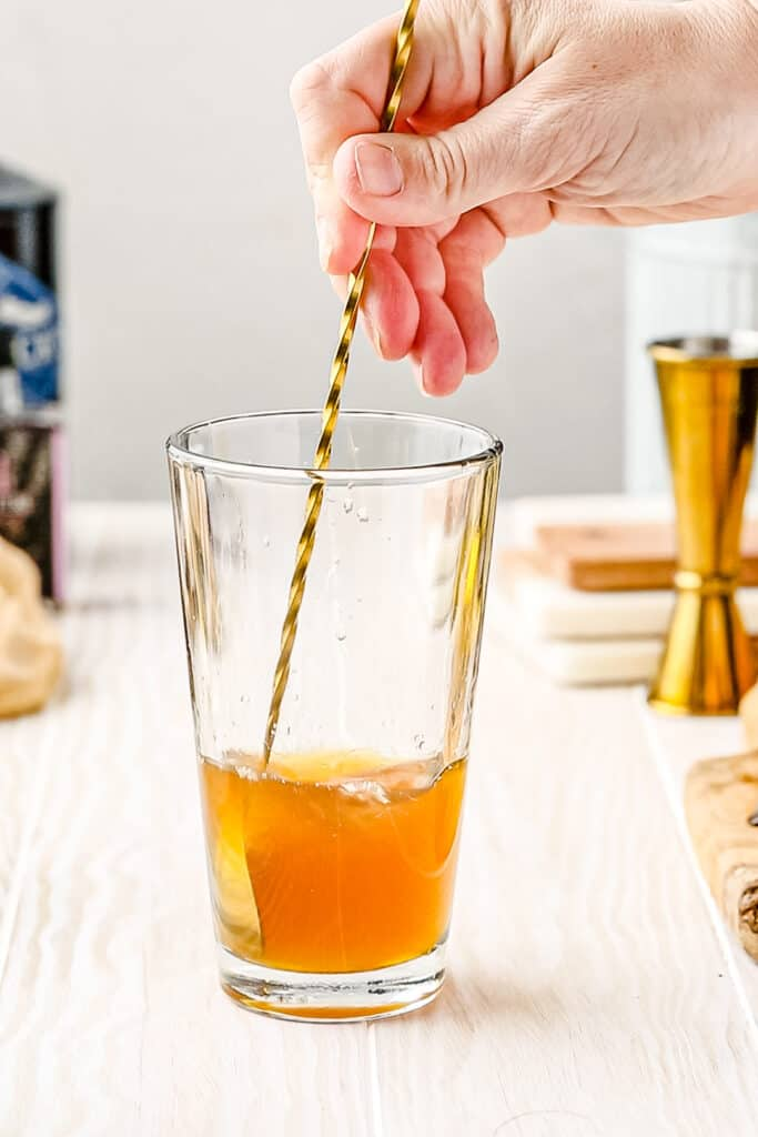 stirring cocktail with spoon to dissolve the honey