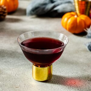 black heart cocktail with mini pumpkins in the backround